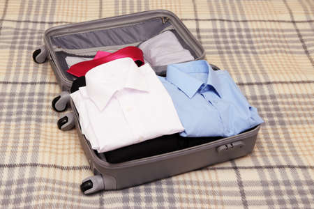 Open grey suitcase with clothing on plaid Stock Photo - 17768897