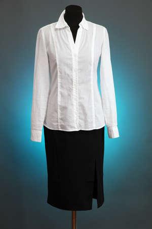Blusa blanca y falda negro con el escudo en el maniqu� sobre fondo de color photo