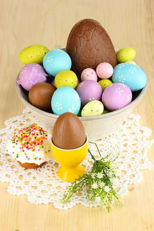 elliptic: Composition of Easter and chocolate eggs and simnel on wooden table close-up