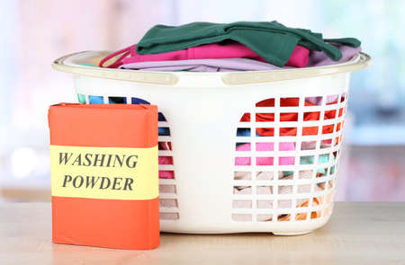 powder room: Clothes in plastic basket on table in room