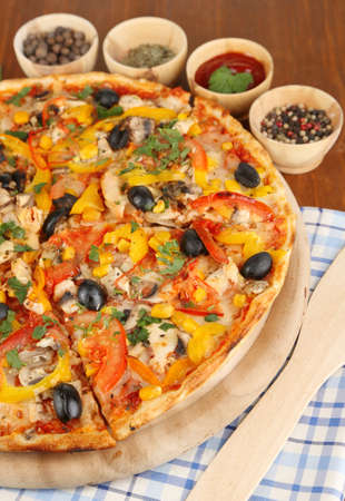 Tasty pizza with kitchen herbs on wooden table close-up Stock Photo - 17769076