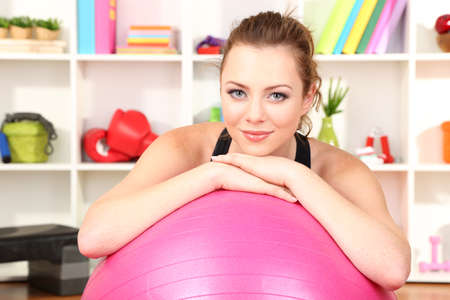 Young woman with gym ball at home photo