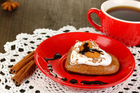 Chocolate cookie in form of heart with cup of coffee on wooden table close-up photo