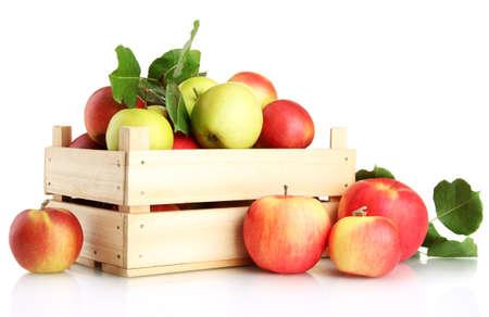 sappige appels met groene bladeren in houten krat, geïsoleerd op wit