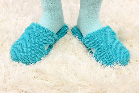 Female legs in color slippers, on carpet background photo