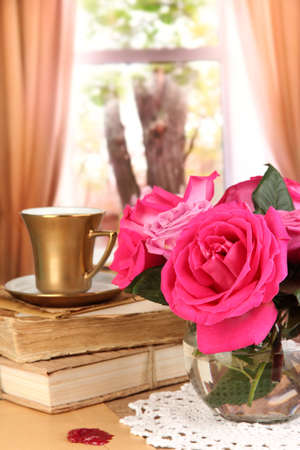Beautiful pink roses in vase on wooden table on window background photo