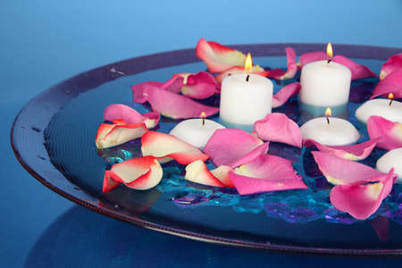 Rose petals and candles in water in vase on blue background close-up photo