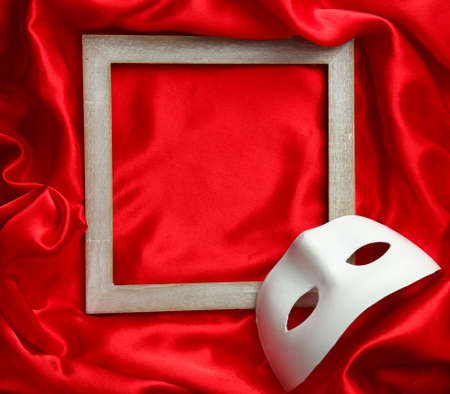White mask and empty frame on red silk fabric photo