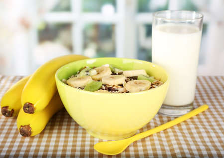 musli: Delicious and healthy cereal in bowl with milk and bananas on table in room