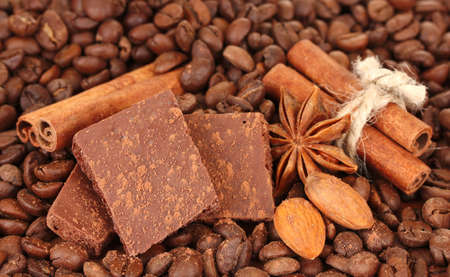 Chopped chocolate with cocoa, spices, on coffee beans background photo