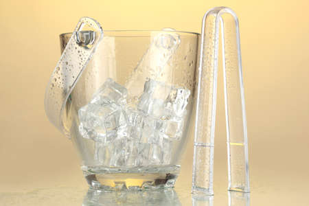 Glass ice bucket on light yellow background photo