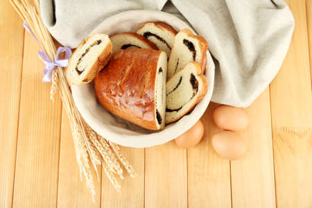 Loaf with poppy seeds in wicker basket, on wooden background photo