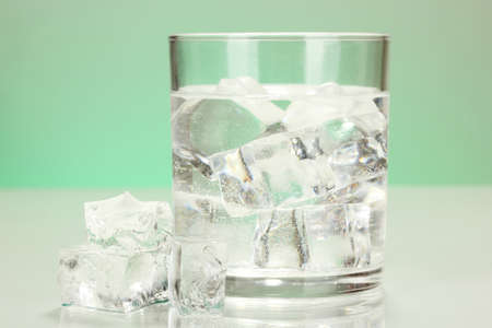 icecube: Ice cubes in glass on light green background