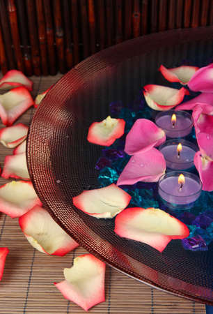 Rose petals and candles in water in vase on wooden table on wooden background photo