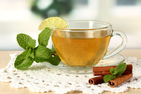 cup: Cup of tea with mint,lime and cinnamon on table in room