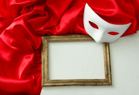 White mask, empty frame and red silk fabric, isolated on white photo