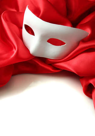 White mask and red silk fabric, isolated on white photo
