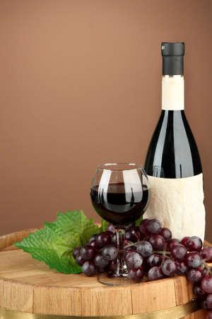 Composición de la botella de vino, el vidrio y la uva, el barril de madera, sobre fondo marrón Foto de archivo - 17771357