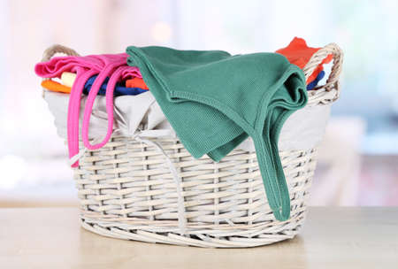 Clothes in wooden basket on table in room Stock Photo - 17771447
