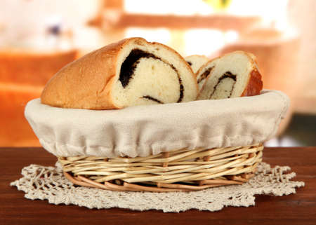 Loaf with poppy seeds in wicker basket, on bright background  photo