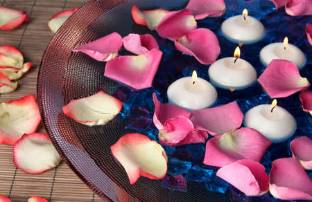 Rose petals and candles in water in vase close-up photo