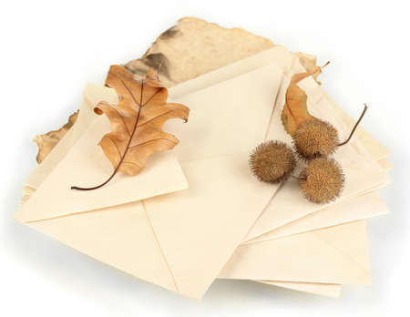 Pile of old letters with dried autumn leafs isolated on white photo