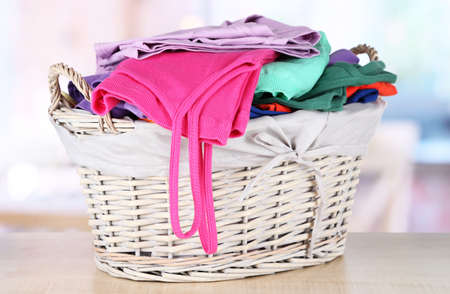 Clothes in wooden basket on table in room Stock Photo - 17826368