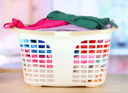 Clothes in plastic basket on table in room photo