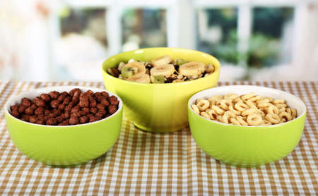 musli: Delicious and healthy cereal in bowls on table in room Stock Photo