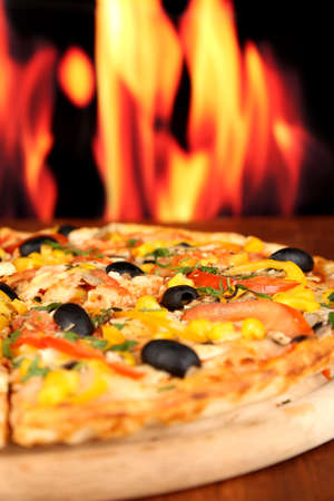 Delicious pizza close-up on wooden table on fire background photo