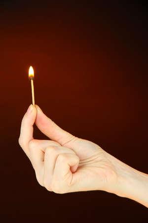 Burning match in female hand, on dark brown background Stock Photo - 17824019