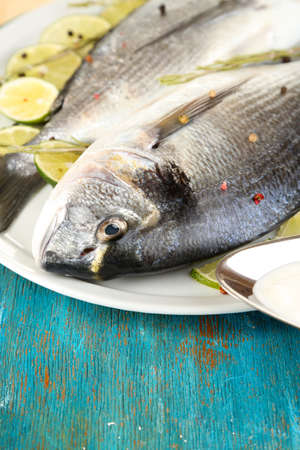 Two fish dorado with lemon on plate on blue wooden table close-up Stock Photo - 17826833