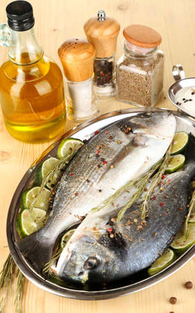 Two fish dorado with lemon on pan on wooden table close-up Stock Photo - 17826773