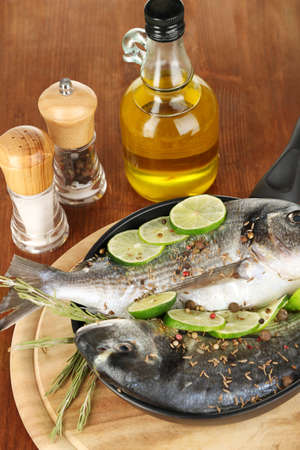 Two fish dorado with lemon on pan on wooden table close-up photo