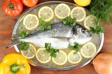 Fresh fish of dorado on tray with lemon and parsley on wooden table Stock Photo - 17826769