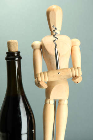 Mannequin with corkscrew and wine bottle, on grey background photo