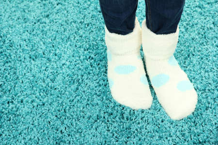 Female legs in colorful socks on color carpet background photo