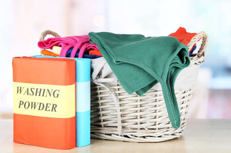 Clothes in wooden basket on table in room photo
