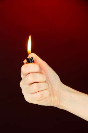 Burning lighter in female hand, on dark red background photo