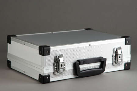 Silvery suitcase on grey background Stock Photo - 17864543