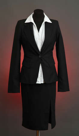 White blouse and black skirt with coat on mannequin on color background photo