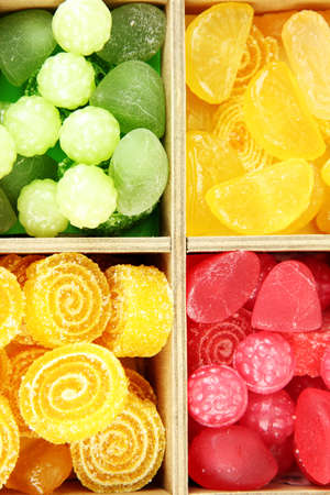 Multicolor candies in wooden box, close up photo