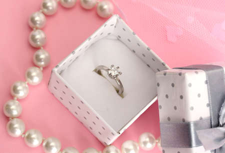 Beautiful box with wedding ring and flower on pink\ background