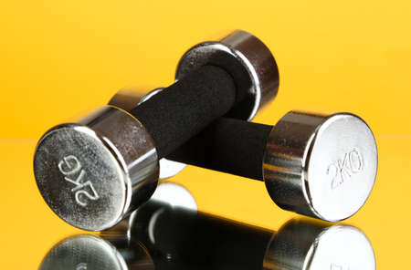 kg: Dumbbells at 2 kg on yellow background Stock Photo