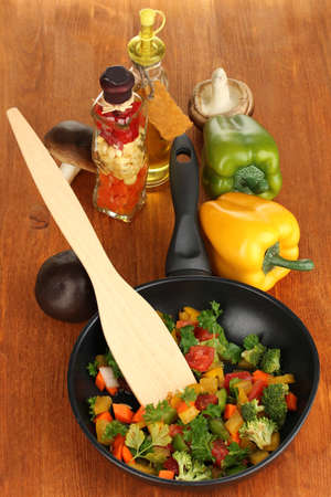 Sliced fresh vegetables in pan with spices and ingredients on wooden table Stock Photo - 17944551
