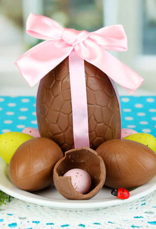 Composition of Easter and chocolate eggs on window background photo
