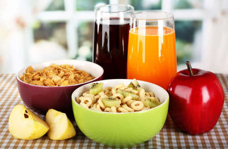 Delicious and healthy cereal in bowls with juice and fruit on table in room photo
