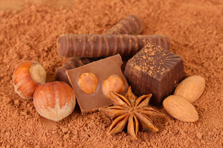 Chocolate sweets with cocoa, on brown background photo