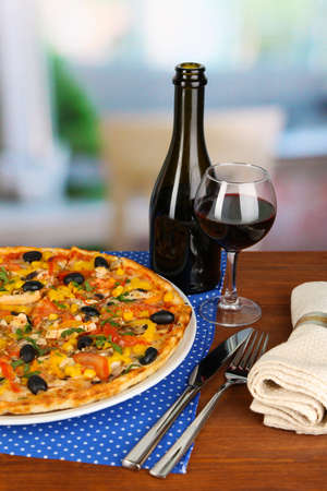 Tasty pizza with wine on wooden table on room background close-up Stock Photo - 17944530