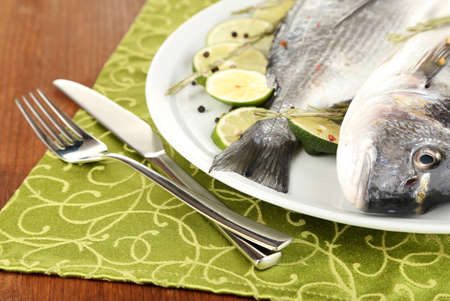 Two fish dorado with lemon on plate on wooden table close-up photo